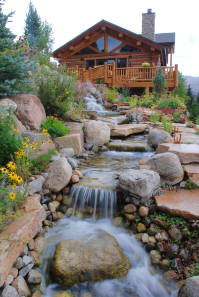 A large slab of natural flagstone forms the cascades and a stairway through the dreamy waterscape - black-eyed Susans and other annual and perennial flowers surround to create a natural look